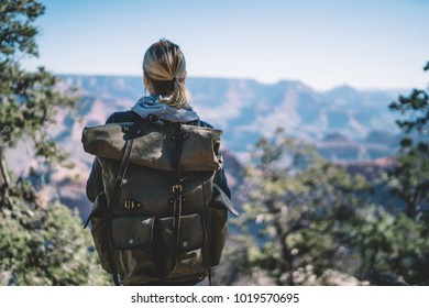 Back view of hipster girl spending recreation actively hiking in mountains with beautiful landscape, female traveler with rucksack exploring wild scenery of Arizona standing on hill looking at nature