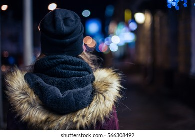 Back view of a hipster girl walking on city street at night
