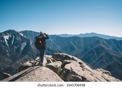 Back view of hipster guy wanderlust enjoying breathtaking scenery from high rock hill, male traveler with backpack recreating explore wild nature looking at mountain peaks landscape on summer vacation