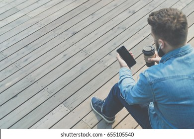 Back view. Hipster man is sitting on bench outside, drinking coffee and using smartphone. Guy in denim shirt is sitting, holding phone and cup of coffee, looking at phone screen. Man chatting online.