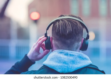 Back view of a hipster man walking on the streets while listening to music on his headphones.