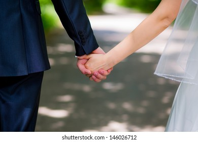 Back view of holding hands couple in love, bride and groom outdoor walking on field.