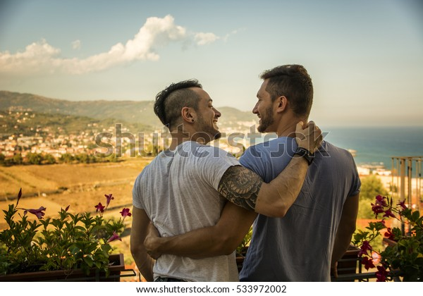Back view of homosexual couple embracing nd looking at each other on background of resort.