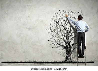 Back view image of businessman drawing graphics on wall