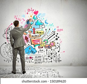 Back view image of businessman drawing sketches on wall