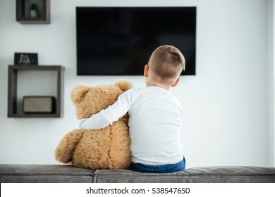 Back view image of cute little boy sitting on sofa with teddy bear waiting for parents at home and watching TV. Look at tv.