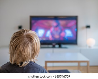 Back view image of cute little blond hair boy sitting on sofa and watching TV.