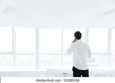 Back view image of man dressed in white shirt talking by phone near big white window.