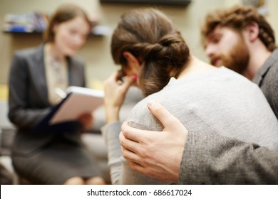 Back view image of young woman crying in couples counseling session with  husband hugging her supportively