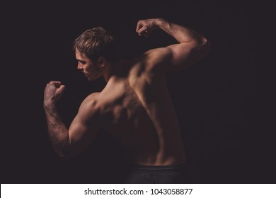 back view image.professional bodybuilder showing his perfect body on the black background.hobby. spending time. activities
