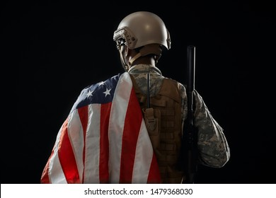 Back view of incognito soldier holding American flag on shoulder and weapon on other. African ranker wearing helmet and uniform returned. Concept of army.
