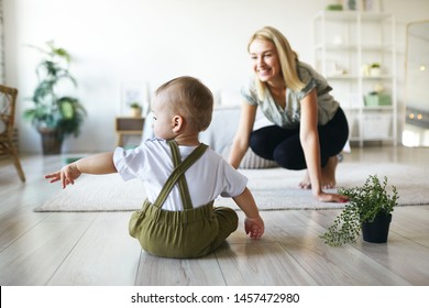Back view of infant child in stylish clothes sitting on floor with plant pot, raising hand, pointing finger sideways, showing something to his young cheerful mother. Family, motherhood and infancy