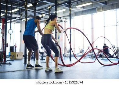 Back view of intercultural man and woman in activewear practicing rope battle in cross training center