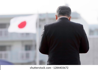 Back view of japanese election orator speaks makes a report to the public with flag