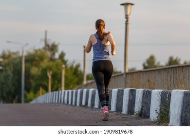 Back view of jogging young woman on the road. Fitness girl running on the bridge