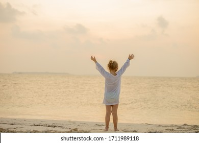 Back view of joyful cute little girl with arms up on beach is enjoying ocean sunset during summer holidays travel. Happy childhood concept