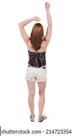 Back view joyful woman celebrating victory hands up. Rear view people collection. backside view person. Isolated over white background. slender blonde in a shorts shows symbol success or hitchhiking