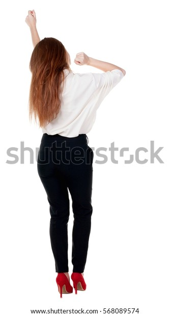 Back view joyful woman celebrating victory hands up. Rear view people collection. backside view person. Isolated over white background. slender redhead in  jeans shows symbol of success or hitchhiking