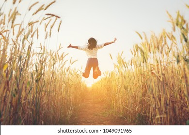 Back view of jumping girl in the barley farm.Freedom concept.
