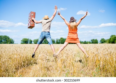 Back view of jumping high female and male holding hands together on the field outdoors copy space background