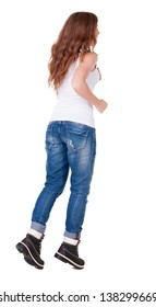back view of jumping  woman  in  jeans. beautiful redhead girl in motion. Joyful girl rushes forward. backside view of person.  Rear view people collection. Isolated over white background.