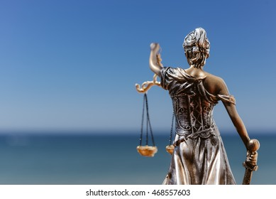Back view of justice, femida or themis goddess sculpture on light copy space background