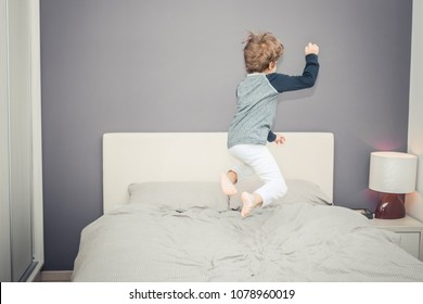 Back view of kid jumping high up on bed and having fun in the evening.