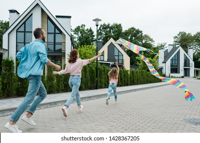 back view of  kid running with colorful kite near parents on street