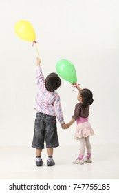 back view of kids holding ballon pointing