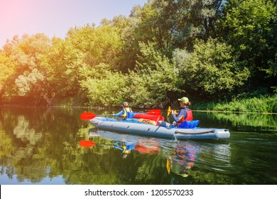 Back view of kids kayaking on the river. Active boy with his sister having fun enjoying adventurous experience with kayak on a sunny day during summer vacation
