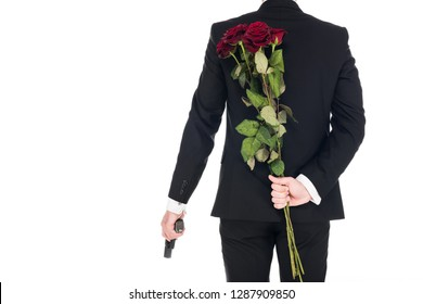 back view of killer in black suit holding handgun and red rose flowers, isolated on white