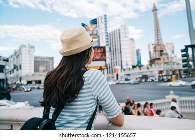 back view of a lady with straw hat watching the tower standing in the busy city. famous tourist attraction in USA. lady backpacker travel alone on spring vacation in Las Vegas.