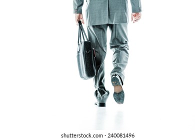 Back view of legs and hands of a businessman carrying a bag isolated on white