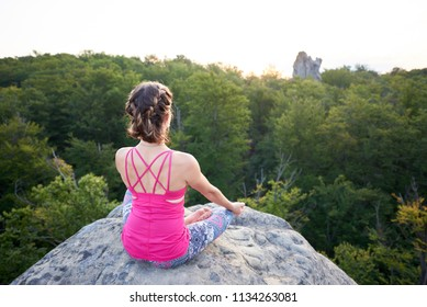 Back view of lit by summer sun young slim tourist woman sitting on top of huge rock doing yoga exercise on green trees tops forest background. Sport, tourism and fitness concept. Siddhasana