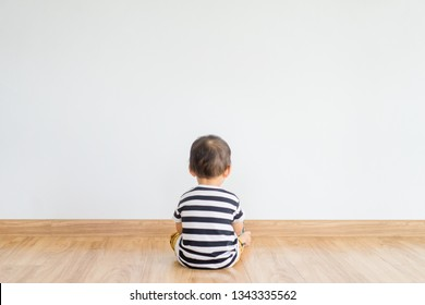 Back view of Little baby boy sitting alone and watching smartphone.