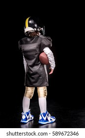 Back view of little boy american football player in uniform holding ball isolated on black