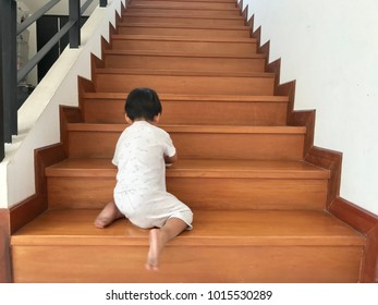 Back view of little boy climbing and playing on the wood stair, wooden staircase for home decoration, modern contemporary house interior design