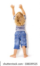 Back view of little boy with hands up on white background.