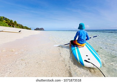 back view of little boy in rashguard holding paddle sitting at surf board enjoying tropical vacation, sun protection concept