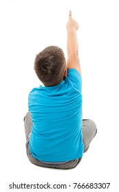 Back view of little boy sitting on floor, points at wall. Rear view. Isolated on white background