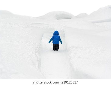 Back view of a little boy in a snowsuit walking through a snowy path with deep snow banks on either side.  Isolated on a white background.