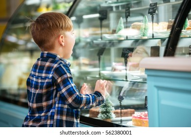 Back view of little boy standing and choosing cake in showcase