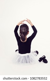 Back view of little girl in black and white dress of ballerina sitting with pointe shoes on white background.