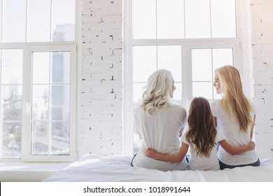 Back view of little girl, her attractive mother and charming grandmother are sitting on bed while spending time together at home. Women's generation. International Women's Day. Happy Mother's Day.