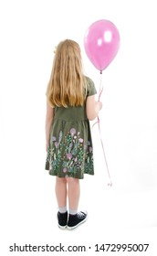 Back view of little girl looking at wall holding pink balloon. Rear view. Isolated on white background