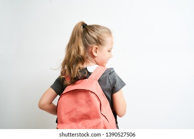 Back view of little girl photographed against white background wearing school uniform dress isolated holding a coral backpack on one shoulder