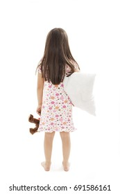 Back view of little girl with pillow and soft teddy in hand, intends to go to bed looking at wall. Rear view. Isolated on white background.