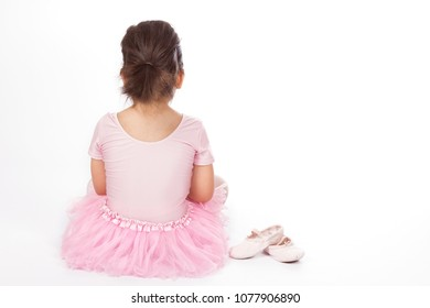 Back view of little girl in pink dress of ballerina sitting with pointe shoes on white background.