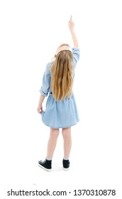 Back view of little girl pointing up above her. Rear view. Isolated on white background