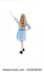 Back view of little girl pointing up at wall. Adorable girl points her hand upwards. Rear view. Isolated on white background